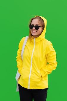 Lächelnde frau in einem gelben regenmantel mit sonnenbrille, die einen toteback auf grünem hintergrund trägt