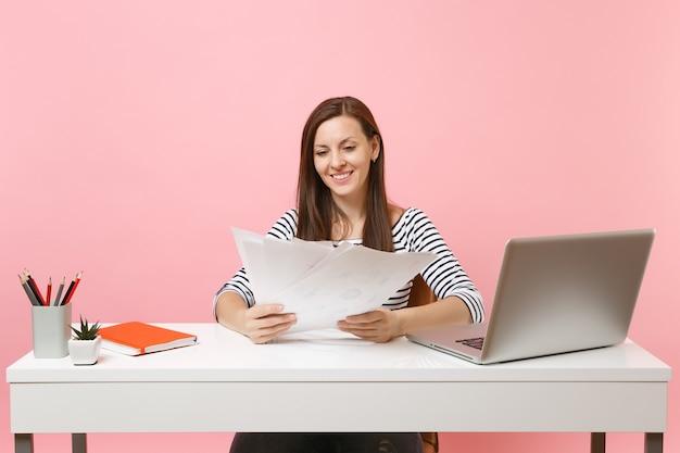 Lächelnde frau in freizeitkleidung, die auf papierdokumenten schaut, an einem projekt arbeitet, während sie mit laptop im büro sitzt