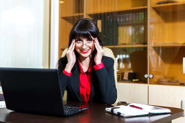 Lächelnde frau in gläsern arbeitet im büro