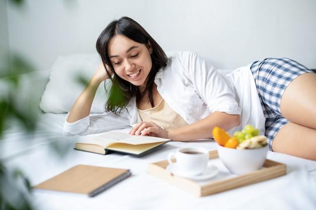 Lächelnde frau in ihrem bett, die ein buch liest. frühstück auf einem brett mit notizblock in der nähe
