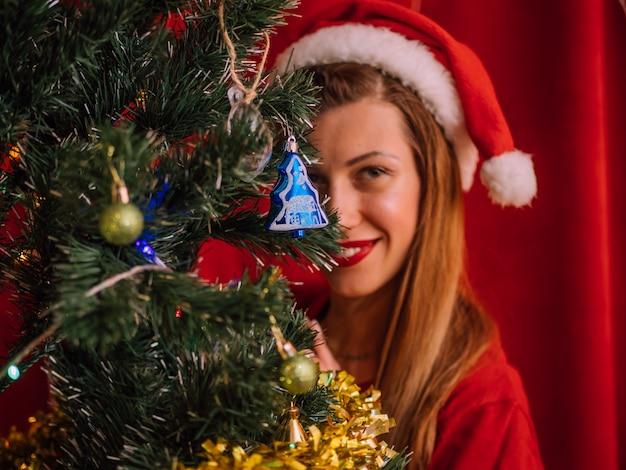 Lächelnde frau in sankt-hut hinter weihnachtsbaum