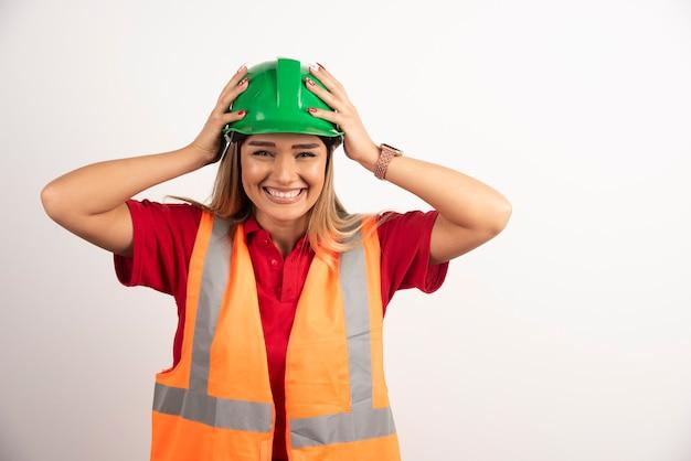 Lächelnde frau in schutzuniform und helm posiert auf weißem hintergrund.