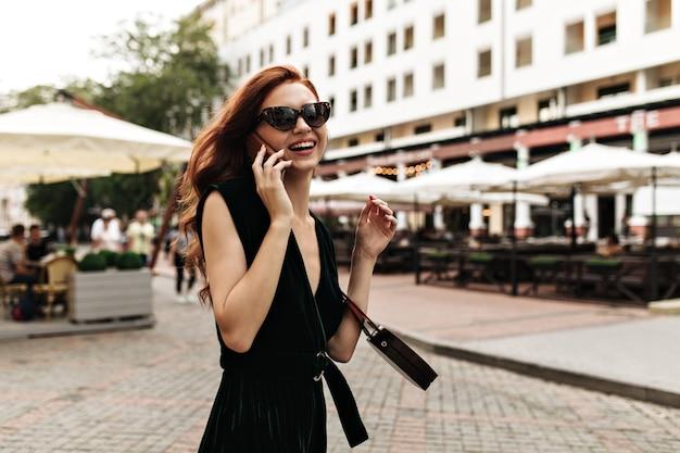 Lächelnde frau in sonnenbrille und kleid spricht am telefon