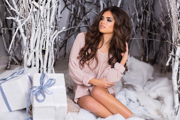 Lächelnde frau in warmen kuscheligen kleidern, die weiße geschenkbox auf winter halten