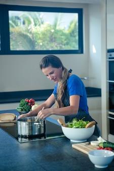 Lächelnde frau kochen gemüse in einem topf auf einem herd