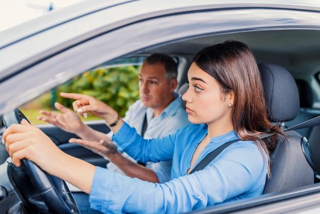 Lächelnde frau lernt, auto mit ausbilder zu fahren. fahren lernen . studentenfahrer t