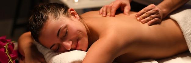 Lächelnde frau masseurin rückenmassage im spa-center