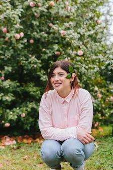 Lächelnde frau mit anlage im haar nahe den rosa blumen, die auf grünen zweigen wachsen