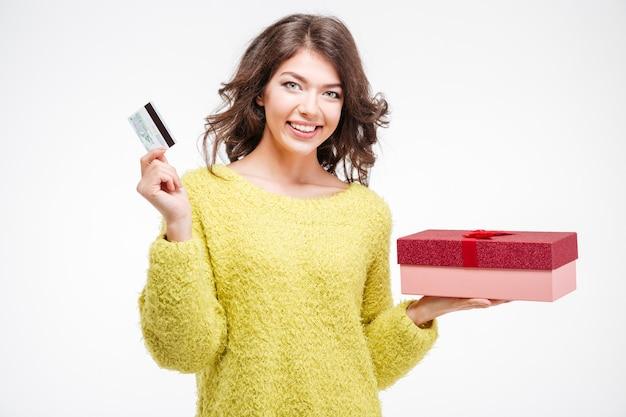 Lächelnde frau mit bankkarte und geschenkbox isoliert auf weißem hintergrund
