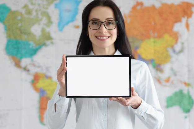 Lächelnde frau mit brille hält tablet mit weißem leerem bildschirm auf dem hintergrund der globalen karte der welt