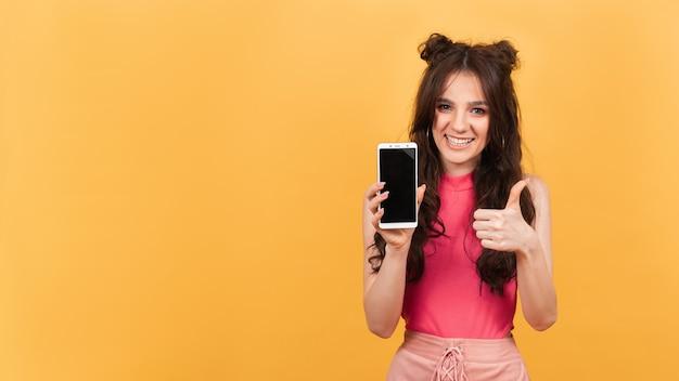 Lächelnde frau mit daumen nach oben hält ein telefon mit leerem bildschirm für mockup auf orangefarbenem hintergrund