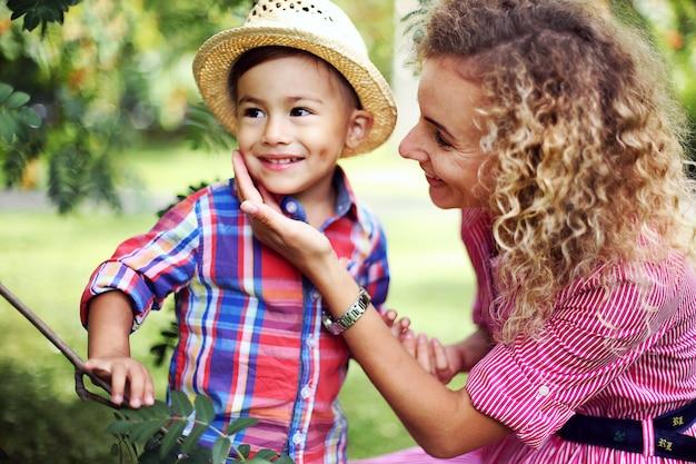 Lächelnde frau mit dem gelockten haar umarmt ihren kleinen sohn in einem sommer park. junges mädchen und kind.