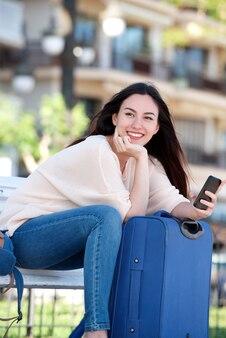 Lächelnde frau mit dem koffer und mobiltelefon, die auf parkbank sitzen