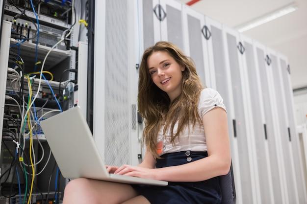 Lächelnde frau mit dem laptop, der mit servern arbeitet