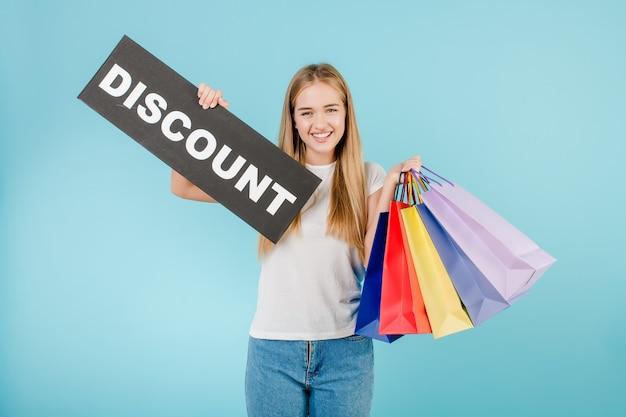 Lächelnde frau mit dem rabattzeichen und bunten einkaufenbeuteln getrennt über blau