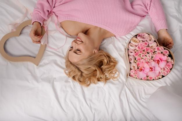 Lächelnde frau mit dem rosa hemd, das auf dem bett nahe dem herzformkasten von rosafarbenen blumen und von abdeckung liegt