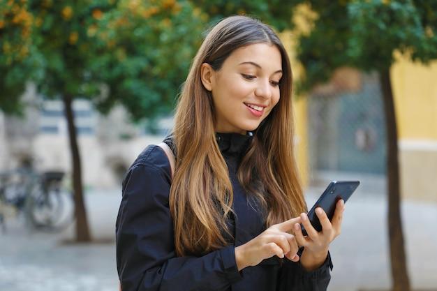 Lächelnde frau mit einem mobiltelefon in der stadtstraße