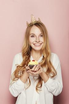 Lächelnde frau, mit einer krone, einen geburtstagskleinen kuchen halten