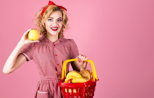 Lächelnde frau mit einkaufskorb und apfel in der hand. glückliches mädchen im supermarkt. kaufrausch. frau mit einkaufswagen.