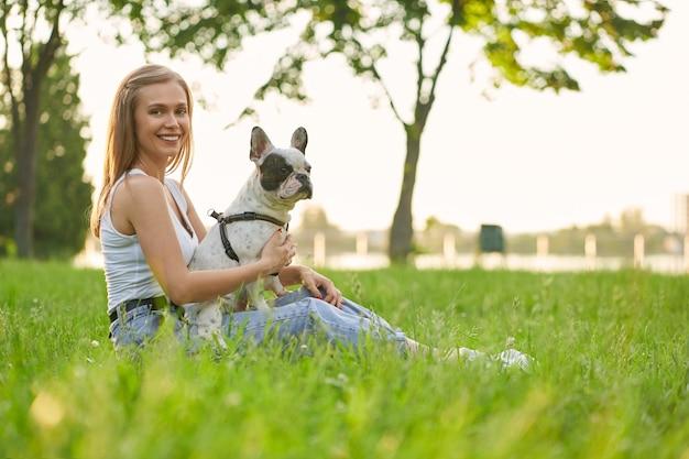 Lächelnde frau mit französischer bulldogge auf gras