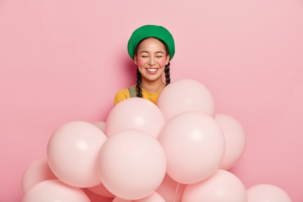 Lächelnde frau mit fröhlichem ausdruck, hält die augen vor vergnügen geschlossen, trägt grüne baskenmütze, steht mit aufgeblasenen heliumballons