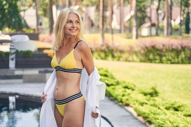 Lächelnde frau mit gelbem badeanzug und weißem weichem bademantel beim ausruhen auf der terrasse des resorts