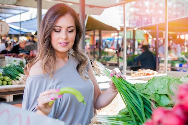 Lächelnde frau mit gemüse auf marktgeschäft. frau wählt frisches gemüse im grünen markt. portrait der schönen jungen frau, die grüne blattgemüse wählt