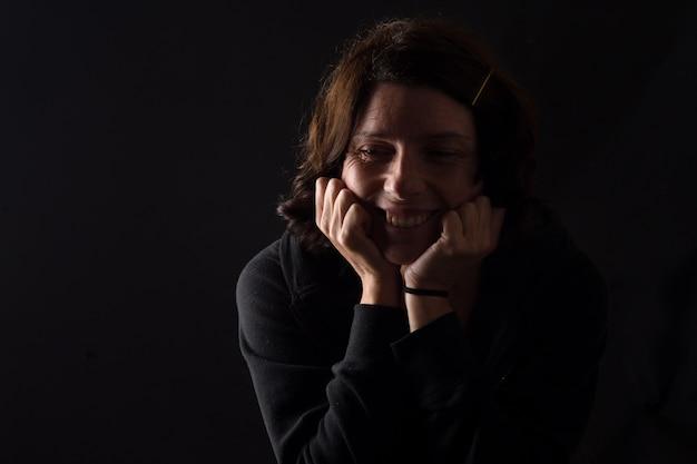 Lächelnde frau mit gesenkten augen auf schwarzem hintergrund