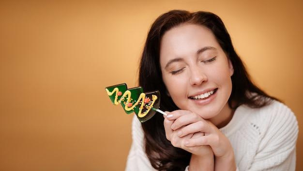 Lächelnde frau mit grünem lutscher über gelbem hintergrundweihnachtsbonbonkonzept