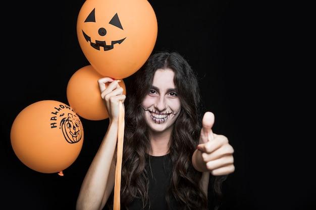 Lächelnde frau mit halloween-ballonen, die gutes zeichen zeigen