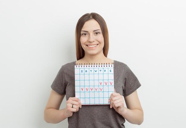 Lächelnde frau mit kalender markiert mit roter markierung. zeitraum.