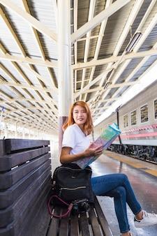 Lächelnde frau mit karte, rucksack und kamera auf bank