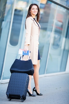 Lächelnde frau mit koffer und pass nahe flughafen
