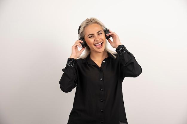 Lächelnde frau mit kopfhörern, die auf weißem hintergrund stehen. hochwertiges foto