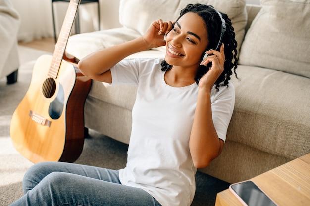 Lächelnde frau mit kopfhörern zu hause, gitarre. hübsche dame mit musikinstrument entspannen sich im zimmer, weibliche musikliebhaberin ruht sich aus?