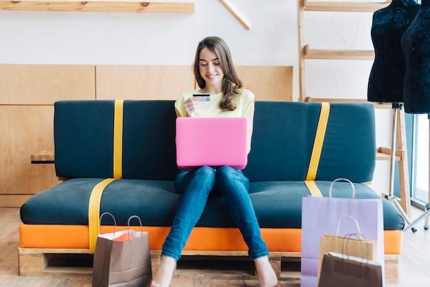 Lächelnde frau mit kreditkarte unter verwendung des laptops