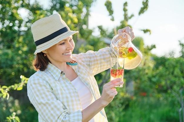 Lächelnde frau mit krug des natürlichen hausgemachten getränks im sommergarten, kräutertee-minze-erdbeeren