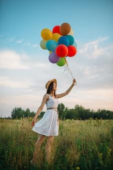 Lächelnde frau mit luftballons, die im grünen feld gehen