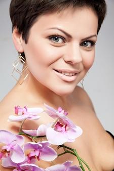 Lächelnde frau mit rosa orchidee. getrennt über weißem hintergrund.