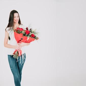 Lächelnde frau mit rosenblumenstrauß