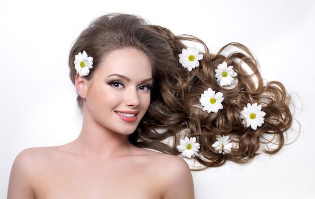 Lächelnde frau mit schönen langen haaren wna blumen darin auf weiß