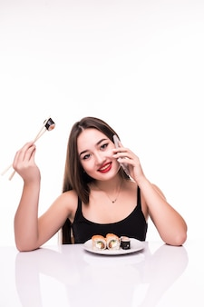 Lächelnde frau mit schwarzen haaren und roten lippen schmecken suushi-rollen, die hölzerne essstäbchen in ihrer hand halten, die auf ihrem telefon sprechen