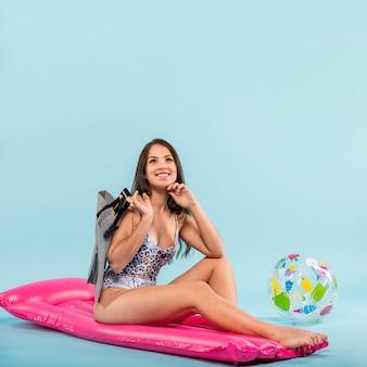 Lächelnde frau mit schwimmflossen auf rosa luftmatte