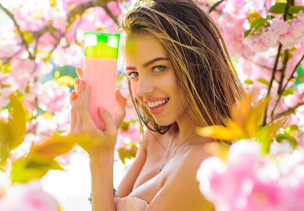 Lächelnde frau mit shampoo. schönes mädchen mit balsam oder conditioner. haarpflege.