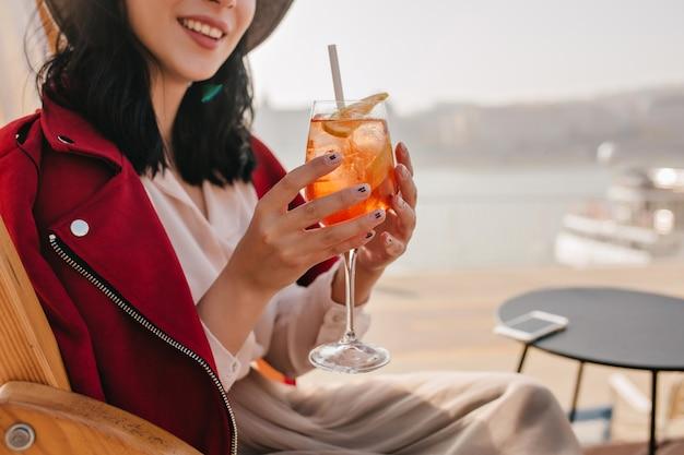 Lächelnde frau mit stilvollem maniküre, der orange cocktail trinkt