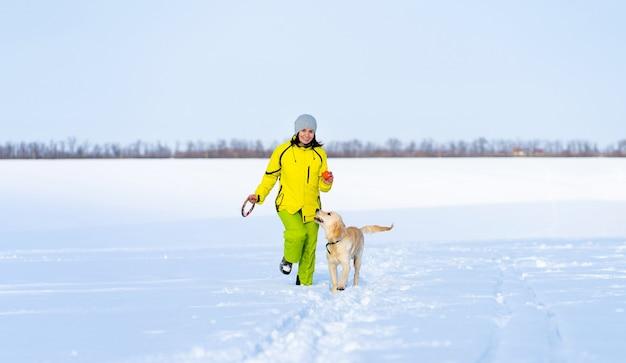 Lächelnde frau mit süßem jungen retriever-hund auf winterspaziergang