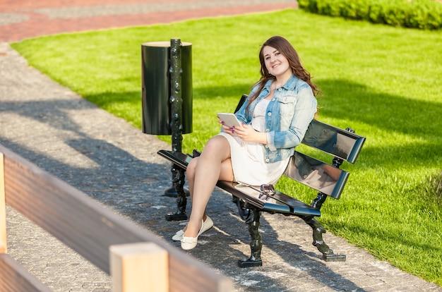 Lächelnde frau mit tablet auf bank im park