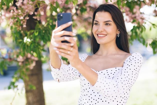 Lächelnde frau mit videoanruf auf dem smartphone in der stadt