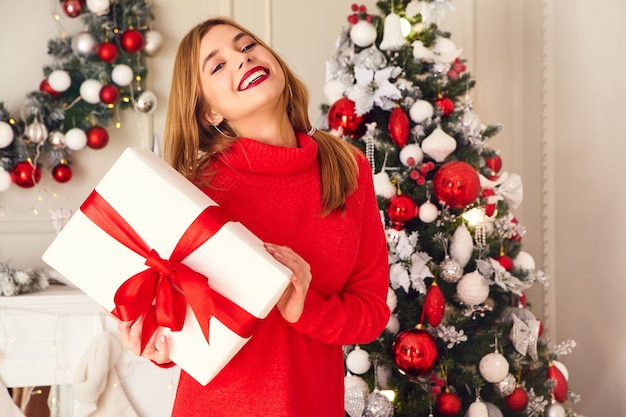 Lächelnde frau mit vielen geschenkboxen, die nahe geschmückten weihnachtsbaum aufwerfen
