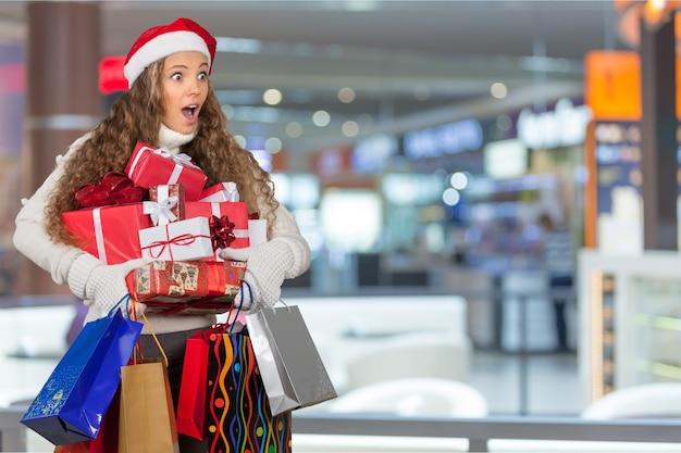 Lächelnde frau mit vielen geschenkboxen im hintergrund